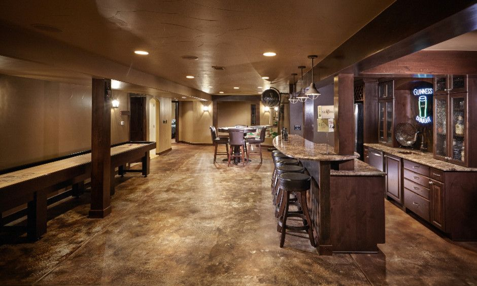 Acid Stained Concrete for a Traditional Basement with a Game Room and Shallow Pond by Highcraft Builders