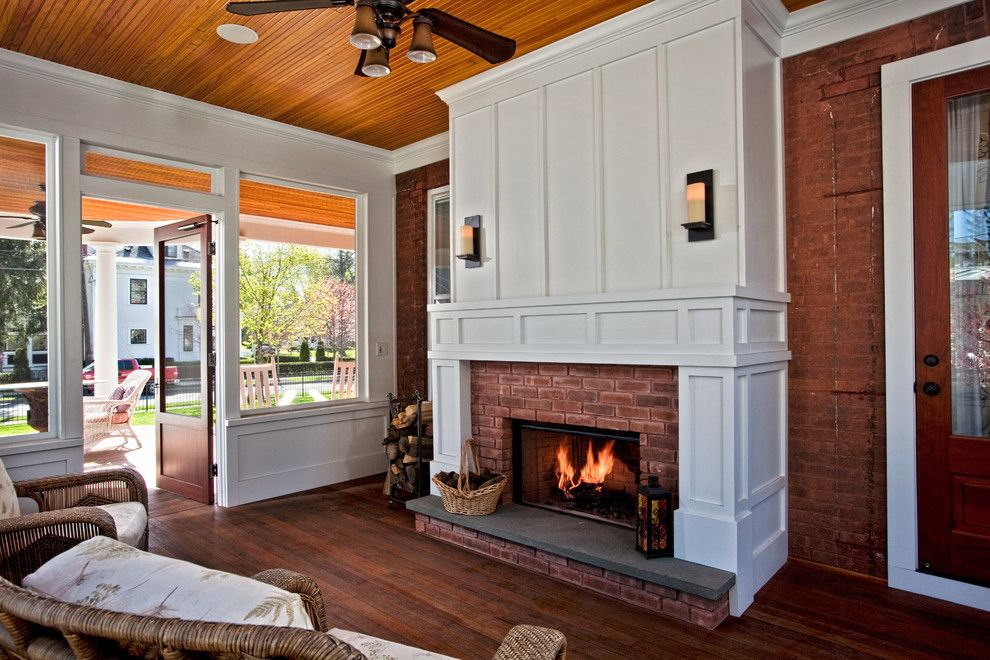 Acme Brick for a Traditional Sunroom with a Wood Fireplace and Changing History by Teakwood Builders, Inc.