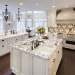 Colonial White Granite for a Traditional Kitchen with a Range Hood and Kitchen by Kanncept Design, Inc.