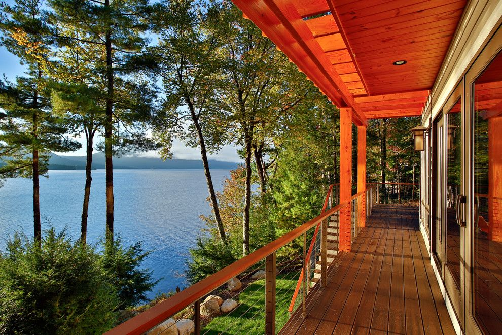 Conestoga Log Cabins for a Rustic Deck with a Engineered Wood Flooring and Bolton Landing Modern Cabin by Teakwood Builders, Inc.