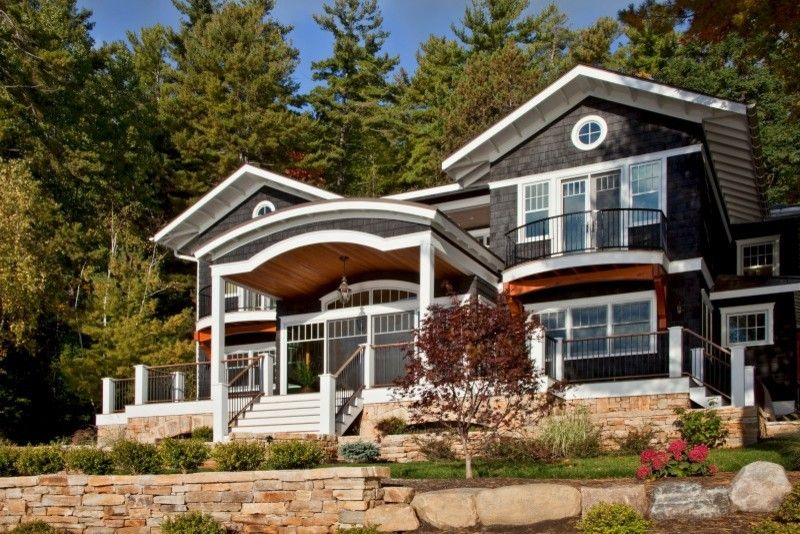 Corinthian Columns for a Traditional Exterior with a Cedar Shake Siding and Legend of the Lake by Teakwood Builders, Inc.