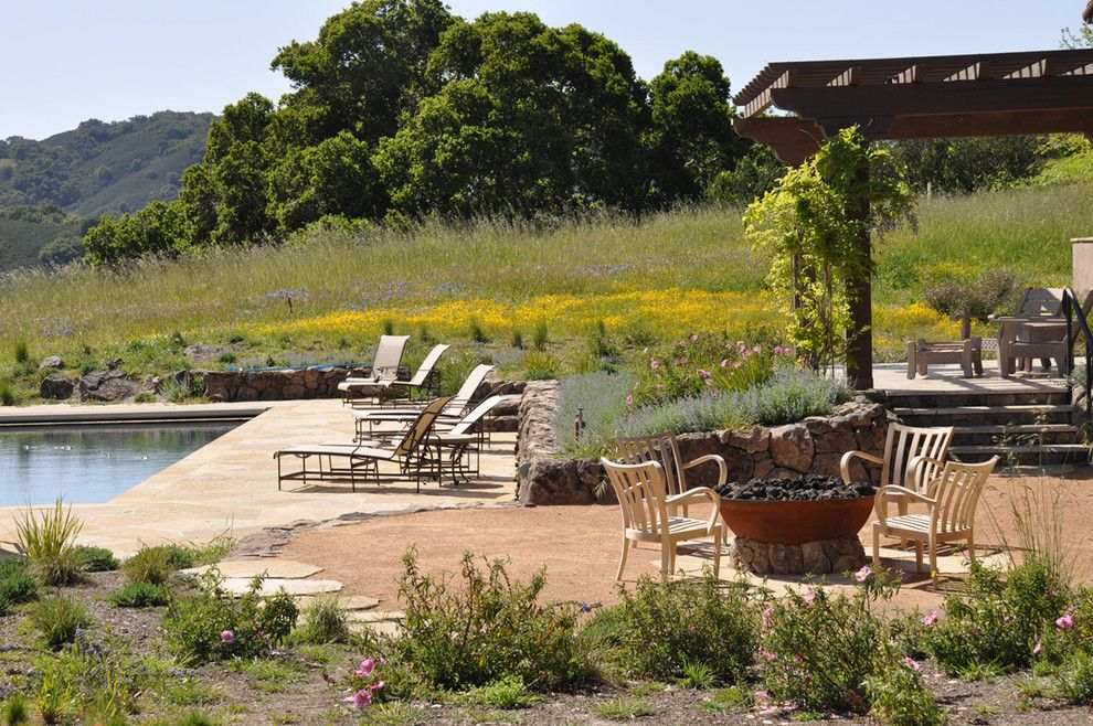 Decomposed Granite Patio for a Rustic Landscape with a Stone Wall and Firepit and Pool by Arterra Landscape Architects