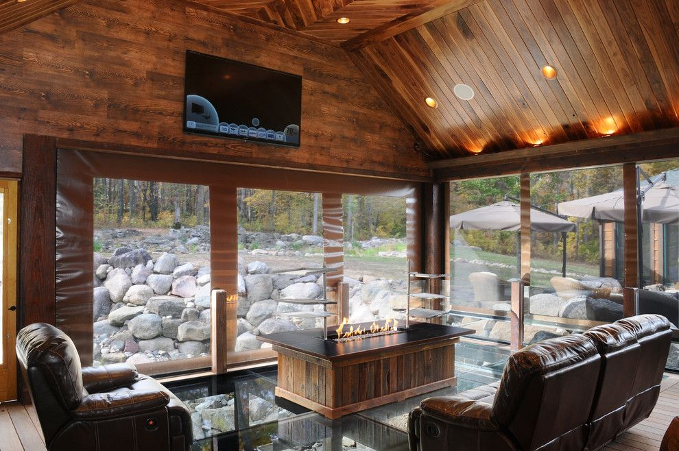 Environmental Stoneworks for a Rustic Porch with a Wood Floor and Outdoor Living Space by Jg Development, Inc.