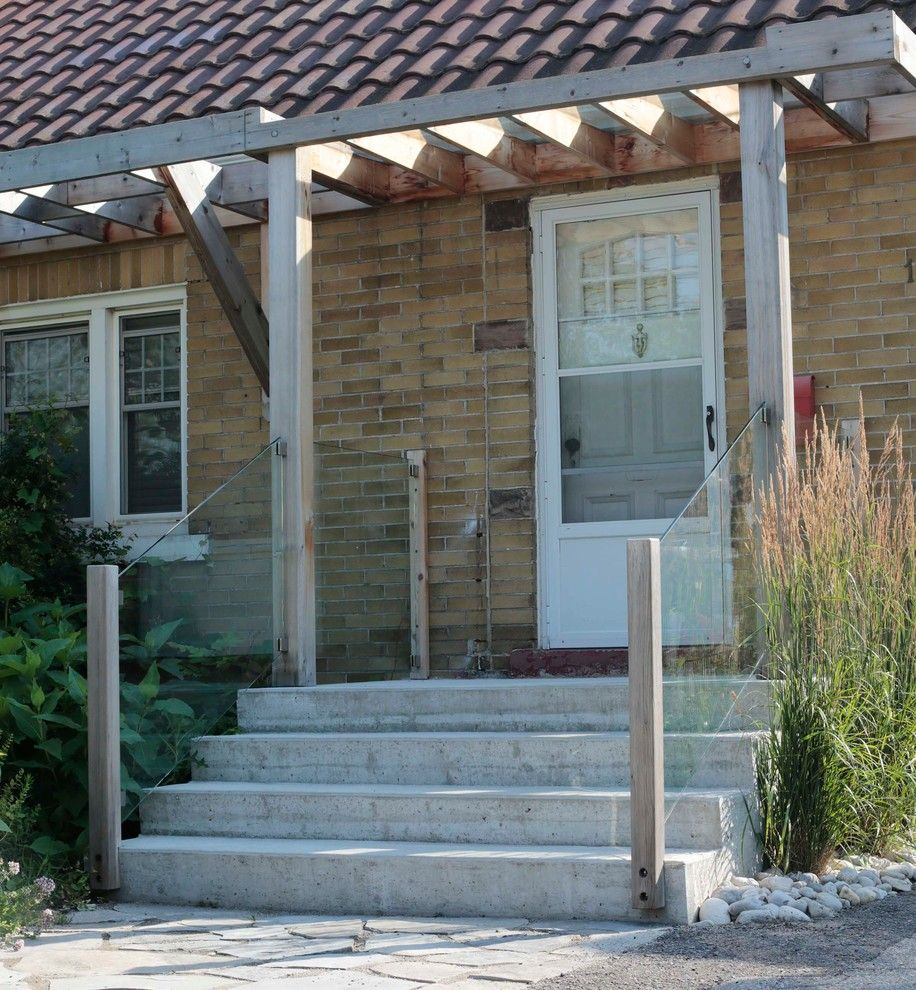 Front Stoop for a Contemporary Entry with a Front Stoop and Front Entry with Pergola and Glass Railing by Heritage Stoneworks Ltd.
