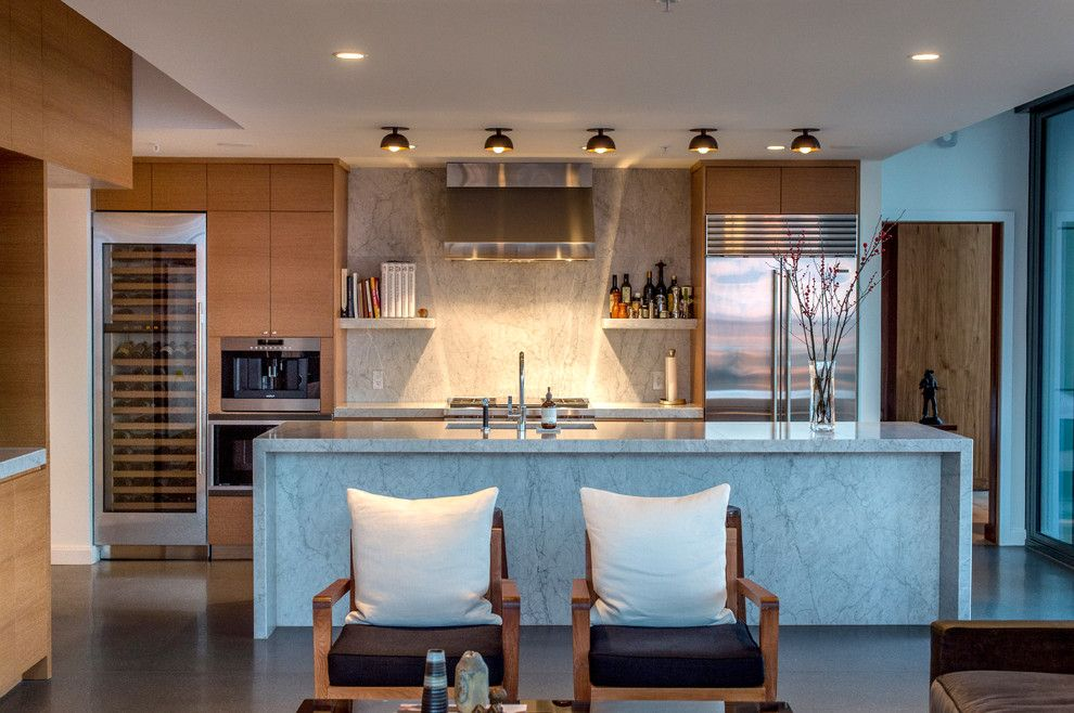 Galley Kitchens for a Contemporary Kitchen with a Waterfall Countertop and White Marble Waterfall Island by Huseby Homes