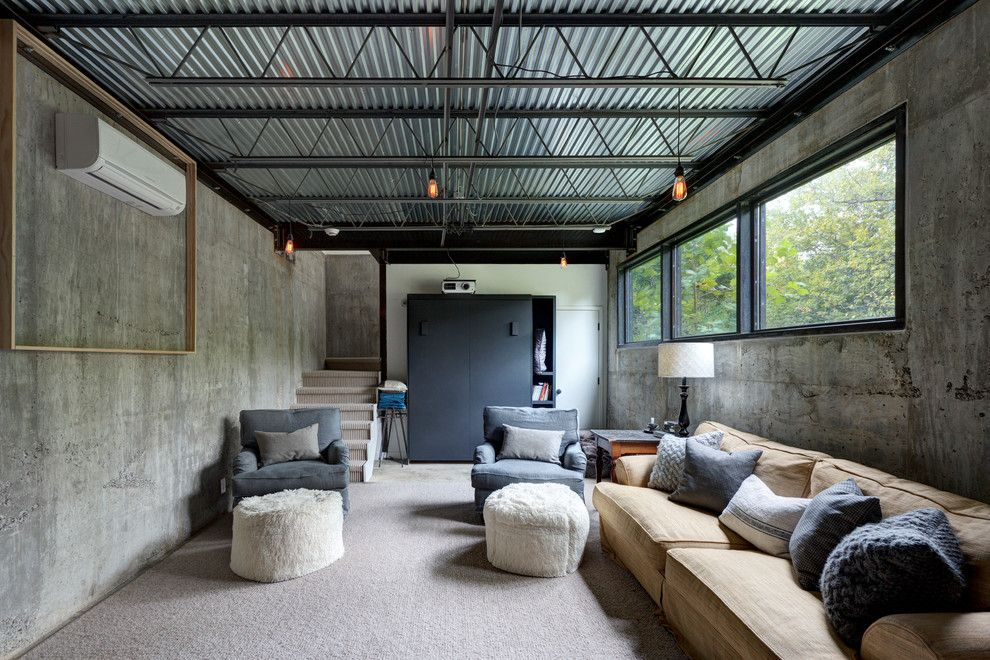 Gonzalez Furniture for a Industrial Basement with a White Drum Lamp Shade and Bouldin Creek Residence by Restructure Studio