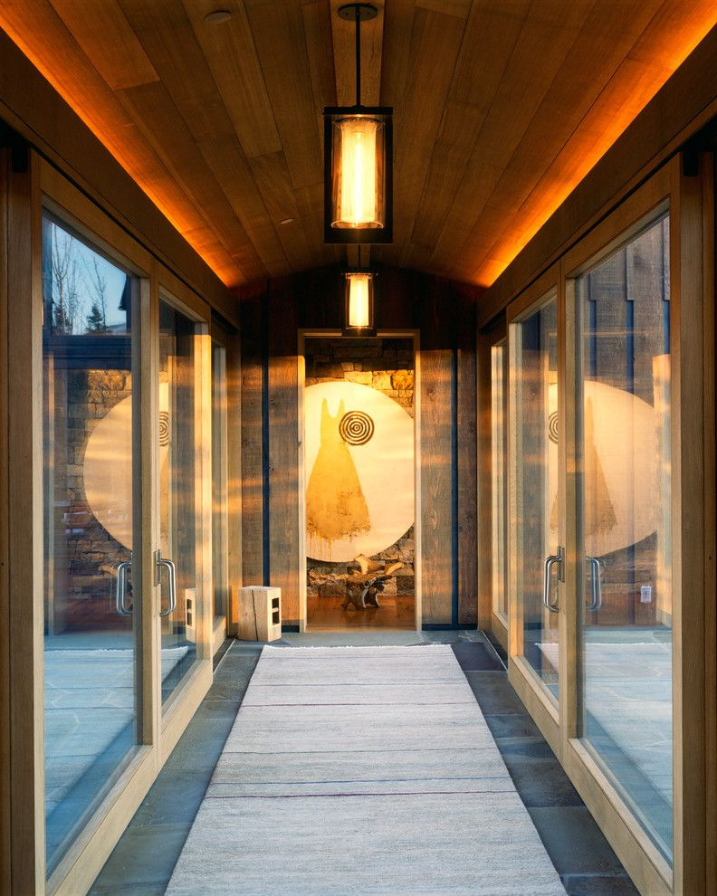 Holly Hunt Lighting for a Rustic Hall with a Wood Wall and Wilson Mountain Residence by Poss Architecture + Planning + Interior Design