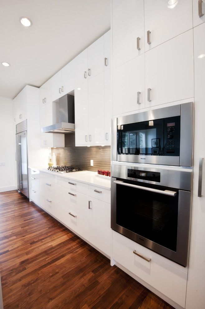 Kodiak Steel Homes for a Contemporary Kitchen with a Wood Floor and Piano White by Fifth Element Homes