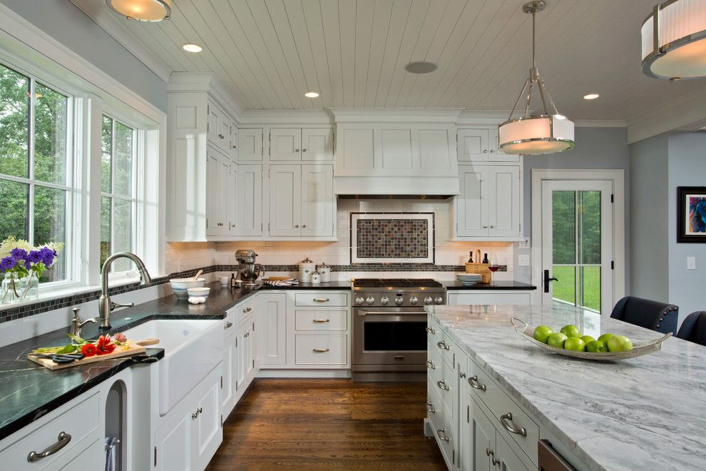 Lapidus Granite for a Farmhouse Kitchen with a Hardwood Flooring and Farmhouse Vernacular by Teakwood Builders, Inc.