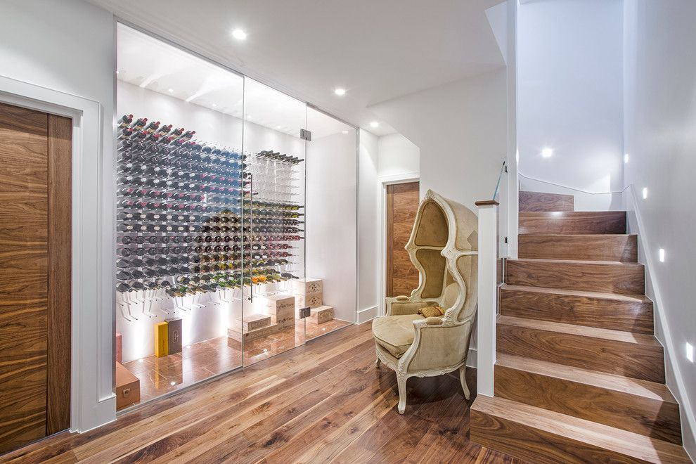 Midwest Basement Systems for a Contemporary Wine Cellar with a Wooden Staircase and a Stunning Wine Room, Which Also Makes a Striking Addition to the Basement Lobby by London Basement