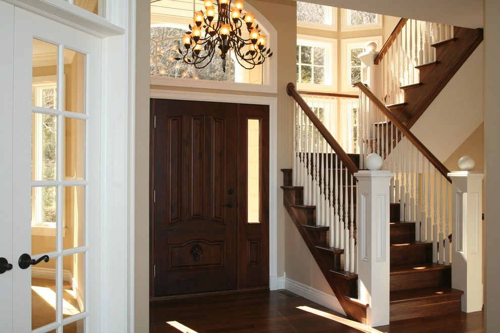 Milliken Doors for a Traditional Entry with a Stair Risers and Staircase with Newels by Thomas & Milliken Millwork, Inc.