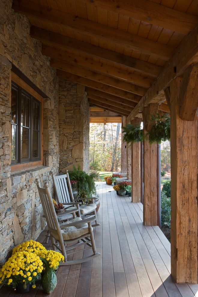 Pirch for a Rustic Porch with a Stone Wall and Stone and Reclaimed Timber Mountain Estate by MossCreek