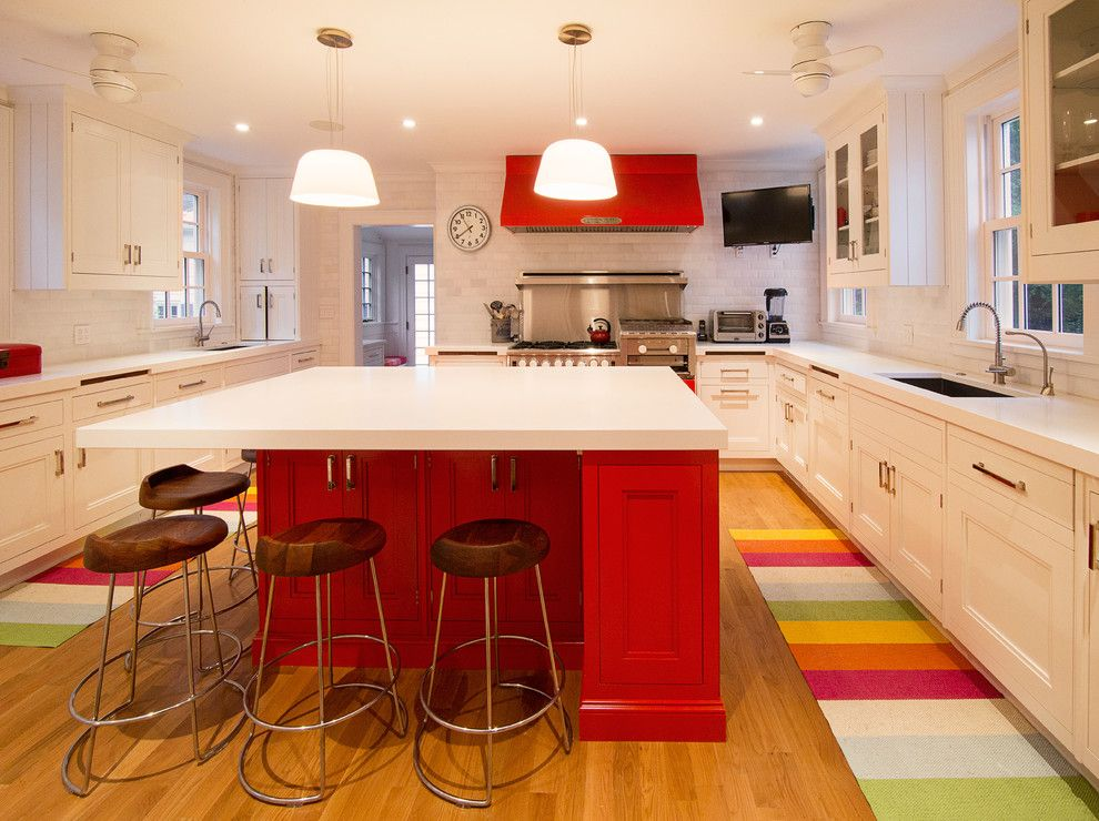 Kitchen with a white countertop and red kitchen by phinney design