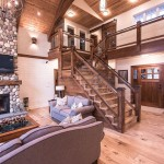 Rustic Living Room Ideas for a Rustic Living Room with a Stone Fireplace and Saskatchewan Lakeside Retreat by Northern Sky Developments