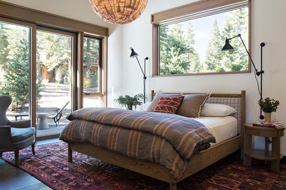 Sierra Pacific Windows for a Rustic Bedroom with a Wingback Chair and Butterfly Cabin by Ward Young Architecture & Planning   Truckee, Ca