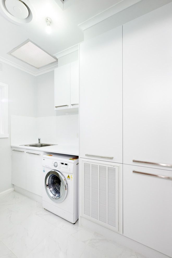 Tankless Water Heater vs Tank for a Modern Laundry Room with a White Crown Molding and Andrew Lee Kitchen and Bathroom Renovation Project by Damco Kitchens
