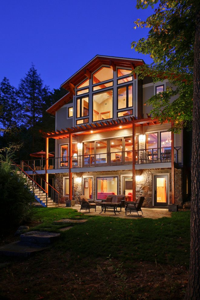 Top Loader vs Front Loader for a Rustic Exterior with a Night Lighting and Bolton Landing Modern Cabin by Teakwood Builders, Inc.
