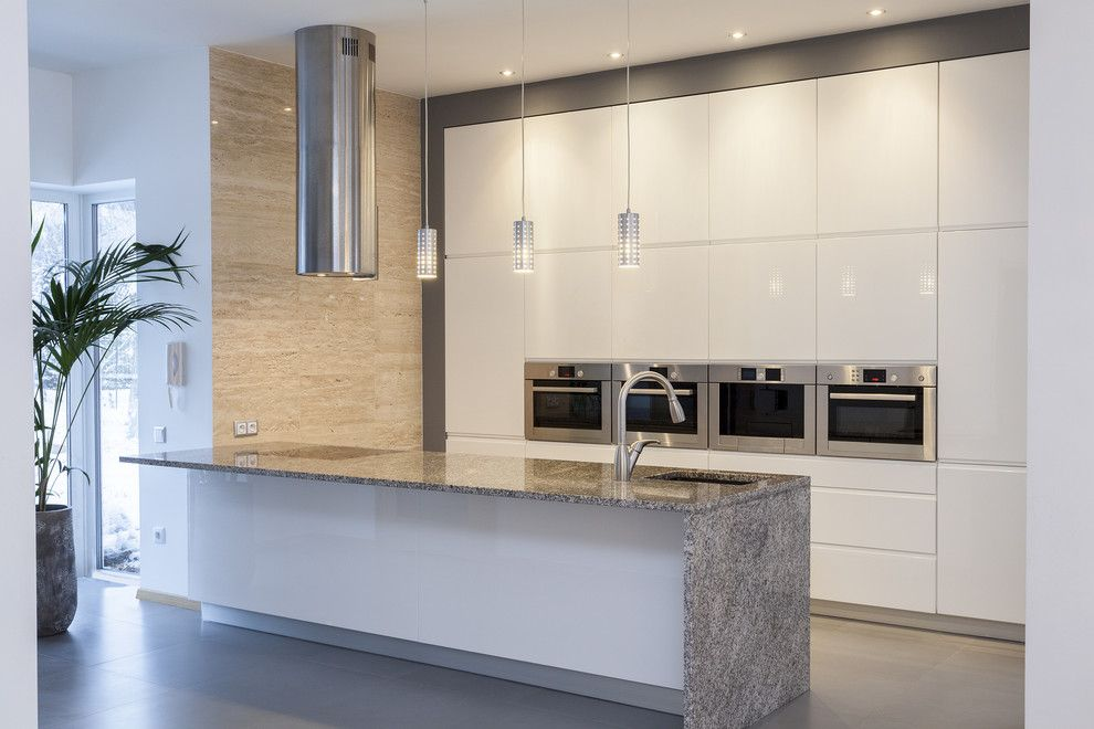 Waterfall Countertop for a Contemporary Kitchen with a Stainless Hood and Kitchens by Modern Style Construction Llc
