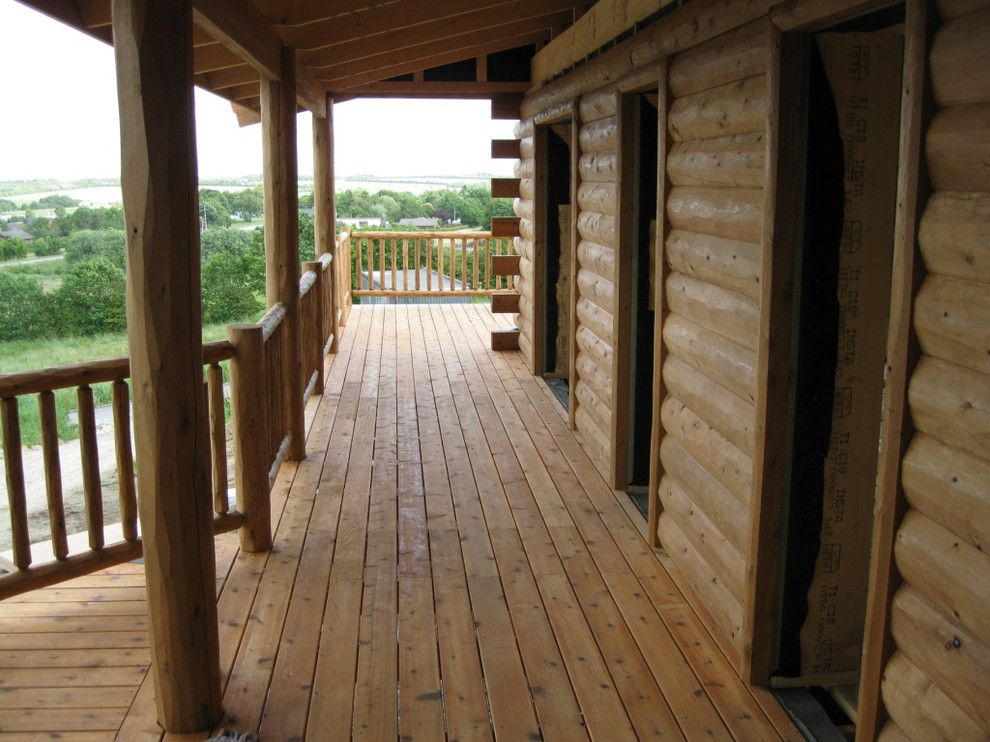 Woodhaven Lumber for a Rustic Porch with a Cedar Railing and Half Log Siding, Cedar Porch and Cedar Deck Railing by Woodhaven Log & Lumber