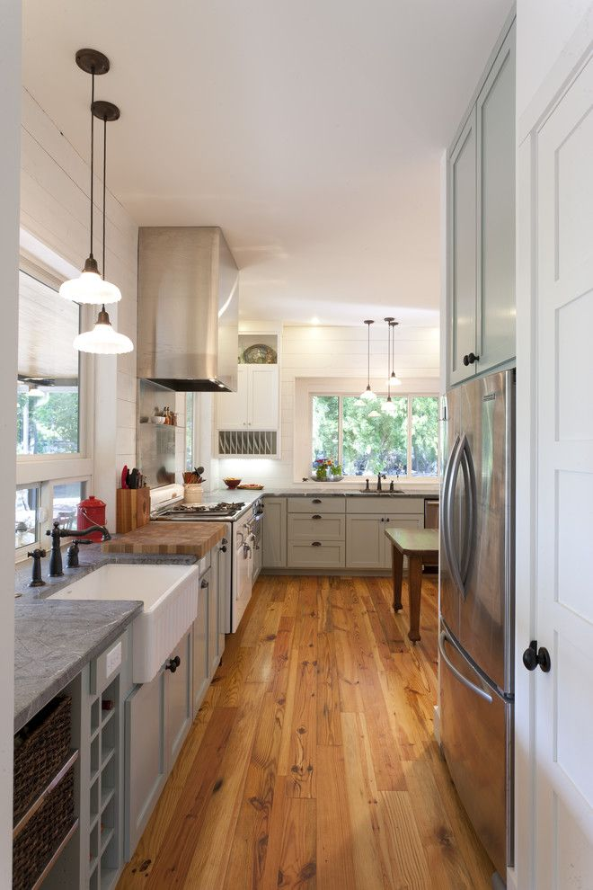 Ohio Valley Flooring for a Farmhouse Kitchen with a Gray Countertop and Farmhouse Kitchen by Rauser Design