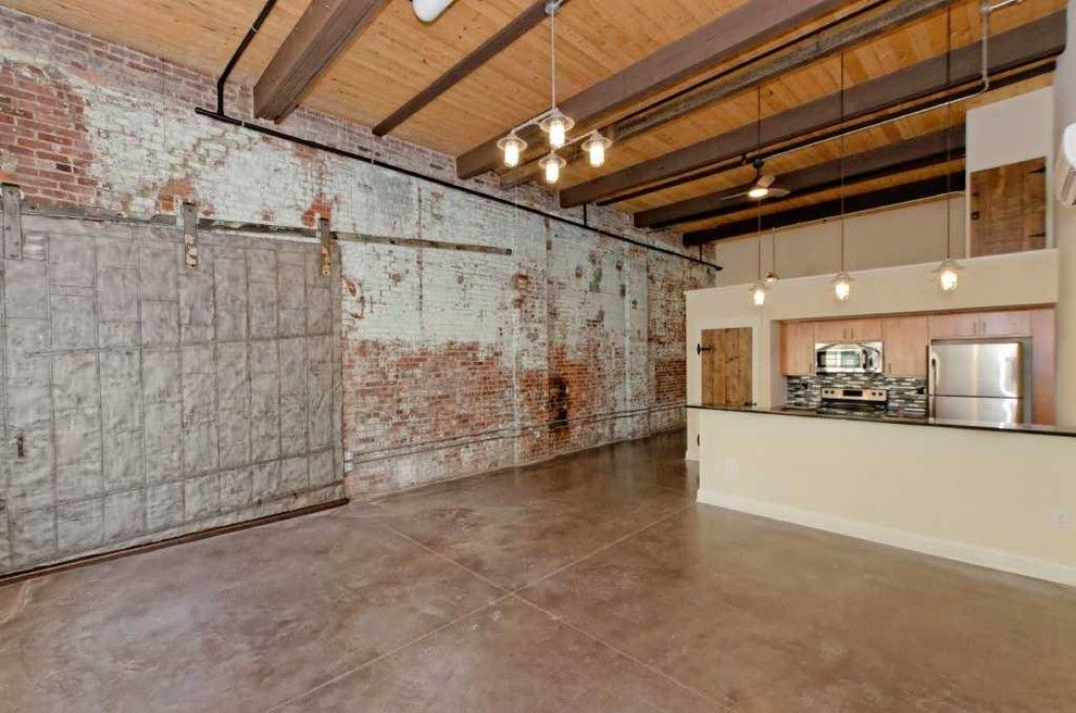 Stadium Lofts Anaheim for a Industrial Living Room with a Barn Door and Window Factory Lofts by Viscusi Builders Ltd.