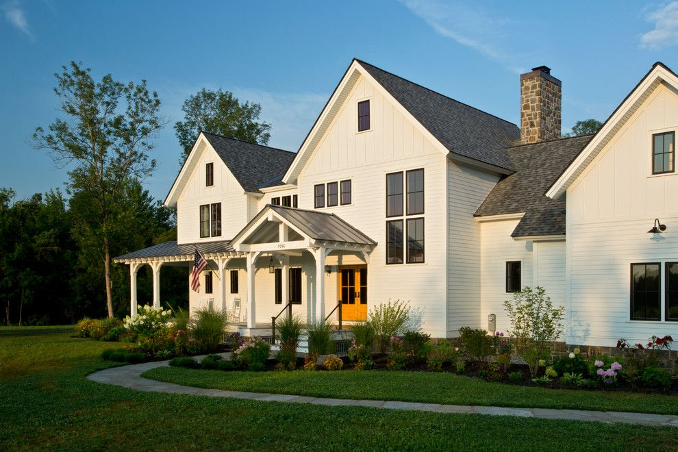 Architectural Millwork for a Farmhouse Exterior with a Mantle and Farmhouse Vernacular by Teakwood Builders, Inc.