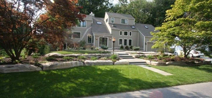 Boulder Lumber for a Contemporary Landscape with a Boulders and Boulder Walls, Bluestone Patios and Plantings by Perennial Landscaping