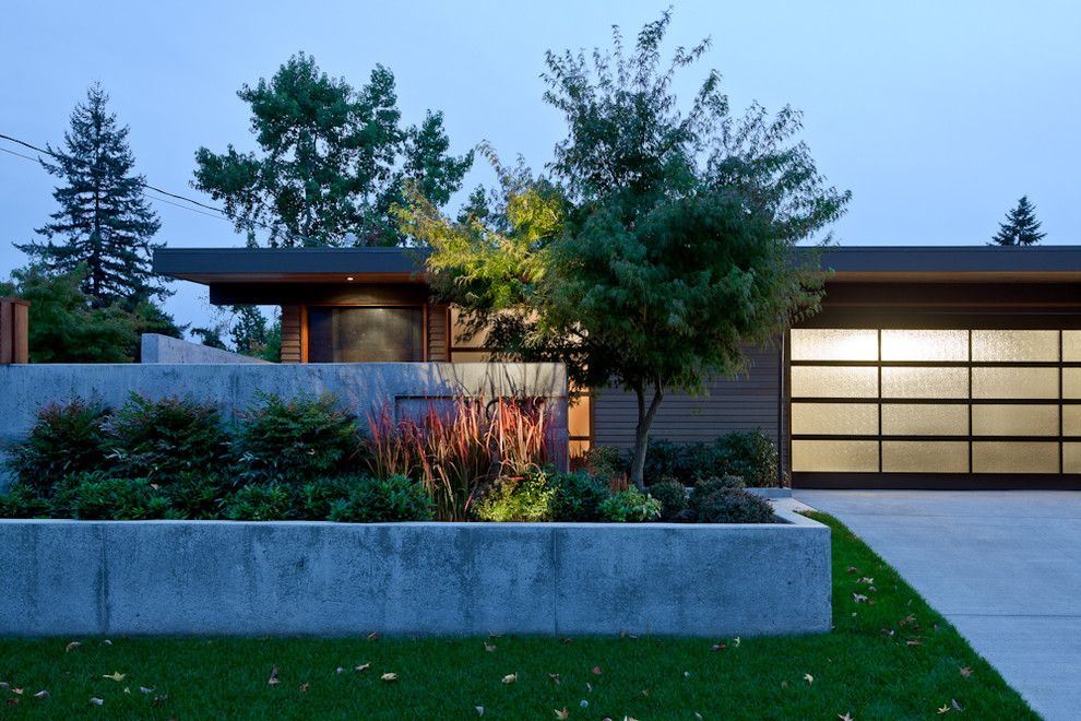 Cinder Block Retaining Wall for a Midcentury Exterior with a Overhang and Enatai Midcentury Modern by Reruchastudio