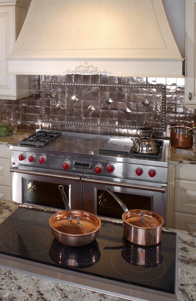 Clarks Appliances for a Traditional Kitchen with a Wolf Dual Fuel Range and Electric Wolf Cooktop with Copper Backsplash by Clarke Appliance Showrooms