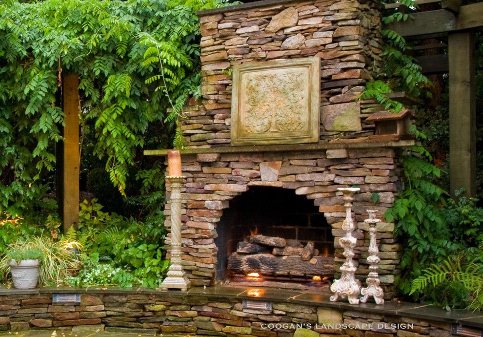 Coogans for a Midcentury Patio with a Curved Fireplace and Outdoor Fireplaces by Coogan's Landscape Design