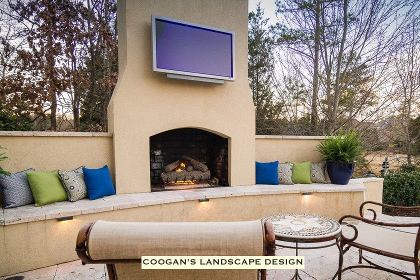 Coogans for a  Spaces with a Fireplace Seating Wall and Backyard Paradise by Coogan's Landscape Design