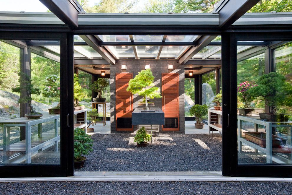 Dads Garage for a Modern Shed with a Glazed Brick Fireplace and Glass House in the Garden by Flavin Architects