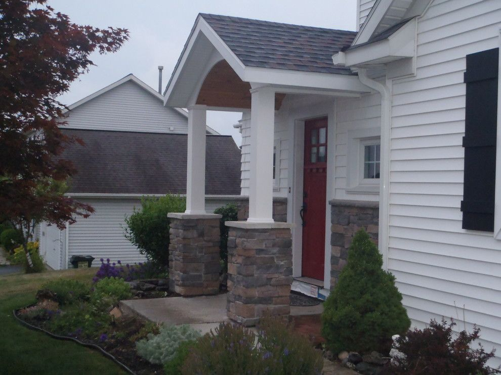 Door Jambs for a Farmhouse Porch with a Door Canopy and Addition with Door Canopy and Stone Work by Bennett Contracting, Inc.