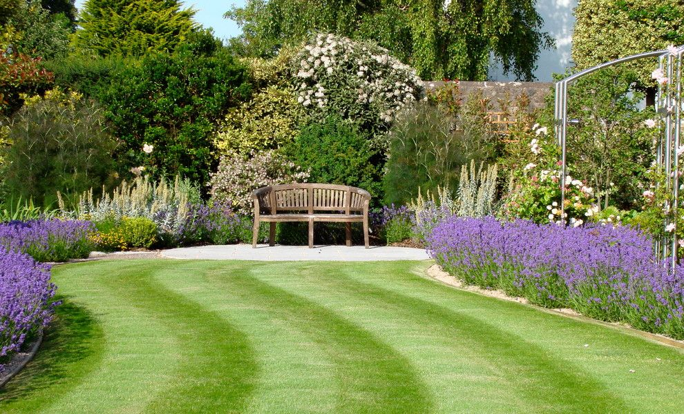 Flowerama for a Traditional Landscape with a Wood Bench and Anchor House by Roger Webster Garden Design
