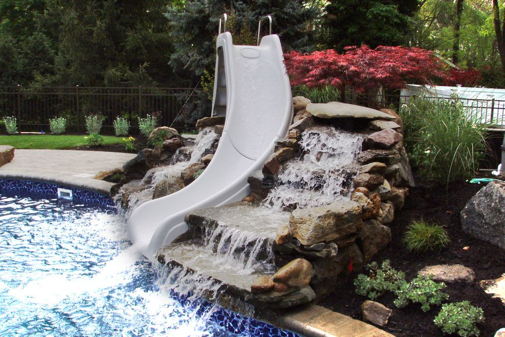 Northport Water for a Contemporary Pool with a Unilock Brussels Block and Natural Pool Design & Waterfall. Melville, Ny. by Autumn Leaf Landscape Design