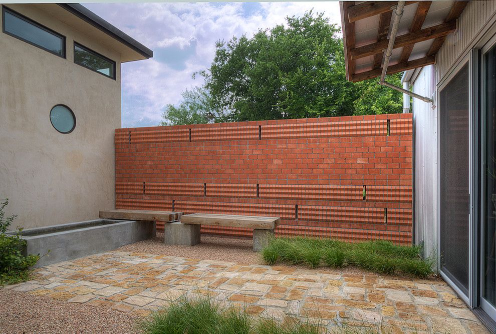 Railroad Tie Retaining Wall for a Modern Patio with a Fence and 3 Homes on a County Courthouse Square by Wintersole Architecture