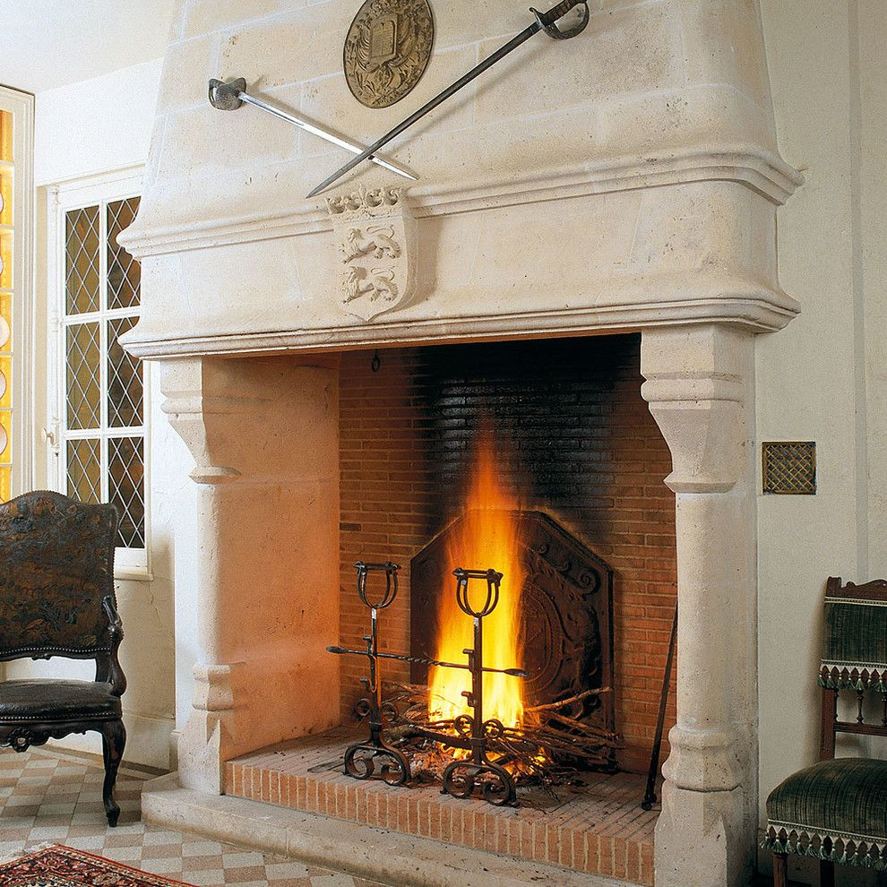 Tailor Lofts for a Mediterranean Living Room with a Stone Mantle and Hand Carved Fireplaces by Ancient Surfaces