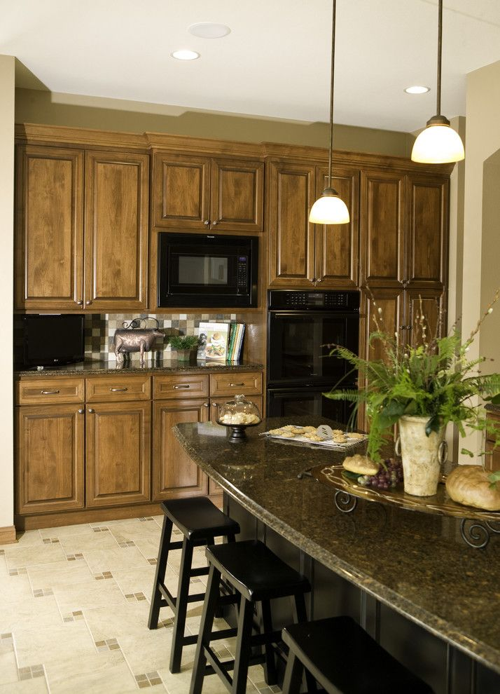 The Seasons of Cherry Creek for a Traditional Kitchen with a Dark Stone Countertop and Custom Arch Cabinets by Cherry Creek, Inc.