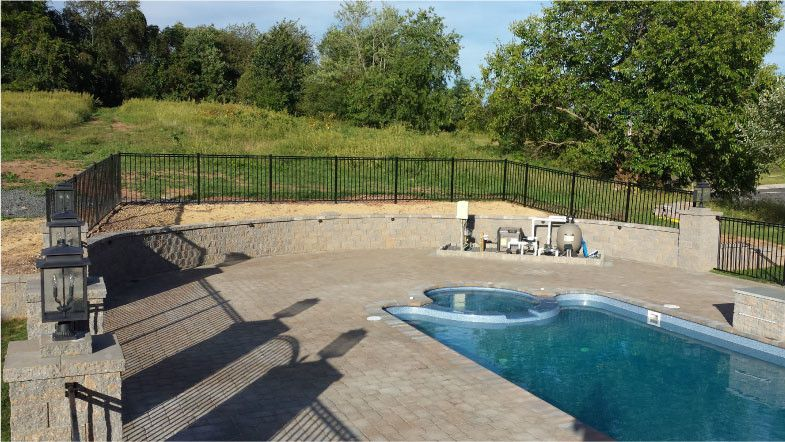 Viking Fence for a Contemporary Pool with a Segmental Retaining Wall 350sf and Pool Deck Hardscaping by Green Construction Group, Inc.
